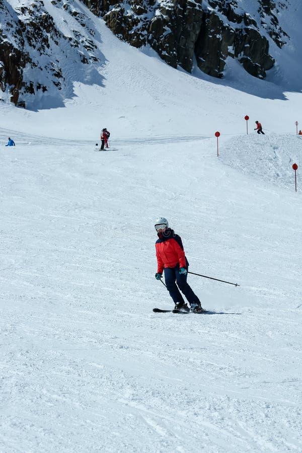 Ο θηλυκός σκιέρ κλίνει προς τα κάτω Ψυχαγωγική δραστηριότητα χειμερινού αθλητισμού στοκ εικόνες