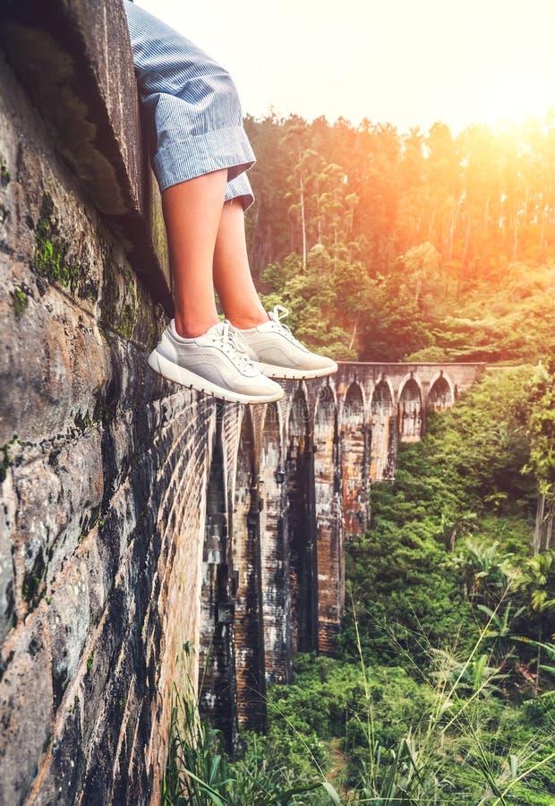 Ο θηλυκός τουρίστας κάθεται στο Demodara εννέα τη γέφυρα αψίδων στη Ella, Σρι Λάνκα: κλείστε επάνω την εικόνα ποδιών στοκ εικόνες
