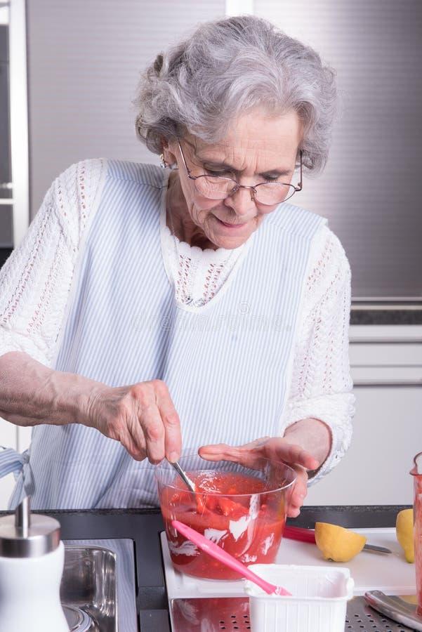 Ο θηλυκός ενεργός συνταξιούχος προετοιμάζει τις φράουλες στοκ εικόνες