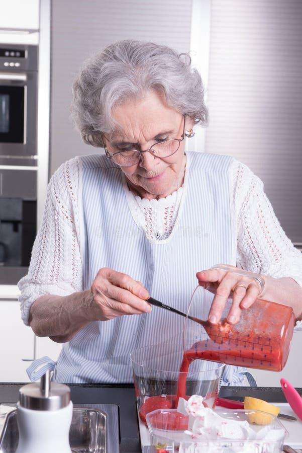 Ο θηλυκός ενεργός συνταξιούχος προετοιμάζει τις φράουλες στοκ φωτογραφία με δικαίωμα ελεύθερης χρήσης