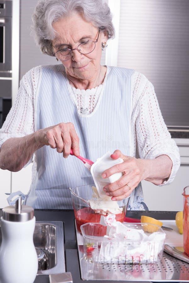Ο θηλυκός ενεργός συνταξιούχος προετοιμάζει τις φράουλες στοκ φωτογραφίες