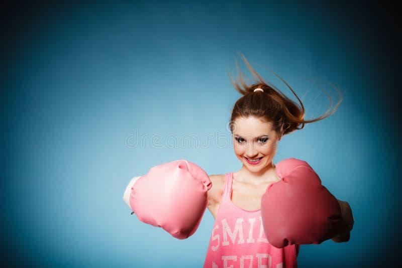 Ο θηλυκός μπόξερ που φορά το μεγάλο ροζ διασκέδασης φορά γάντια στον αθλητισμό παιχνιδιού στοκ φωτογραφία με δικαίωμα ελεύθερης χρήσης