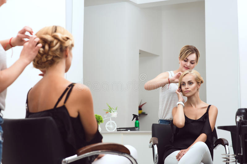 Ο θηλυκός στιλίστας τρίχας πλέκει το όμορφο client& της x27 τρίχα του s στο σαλόνι ομορφιάς στοκ φωτογραφία