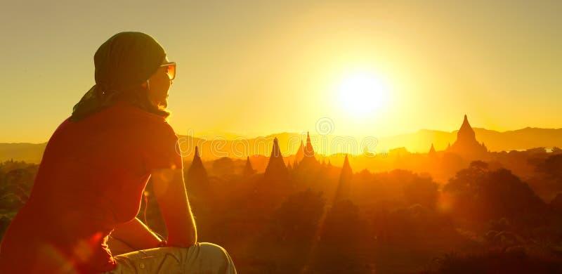 Ο θηλυκός ταξιδιώτης χαλαρώνει τους ναούς σε Bagan το Μιανμάρ Ασία στο ηλιοβασίλεμα στοκ φωτογραφία