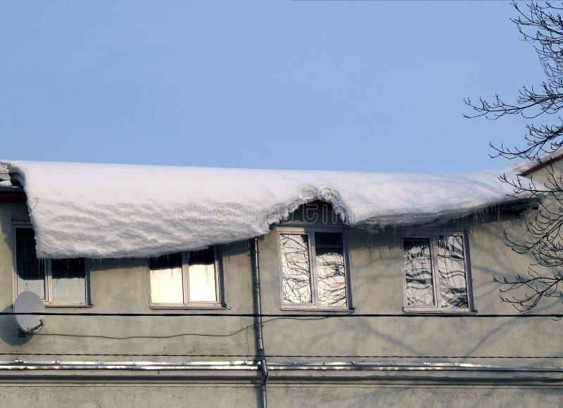 Ο θόλος χιονιού που κρεμά επικίνδυνα κάτω από μια στέγη στοκ φωτογραφία