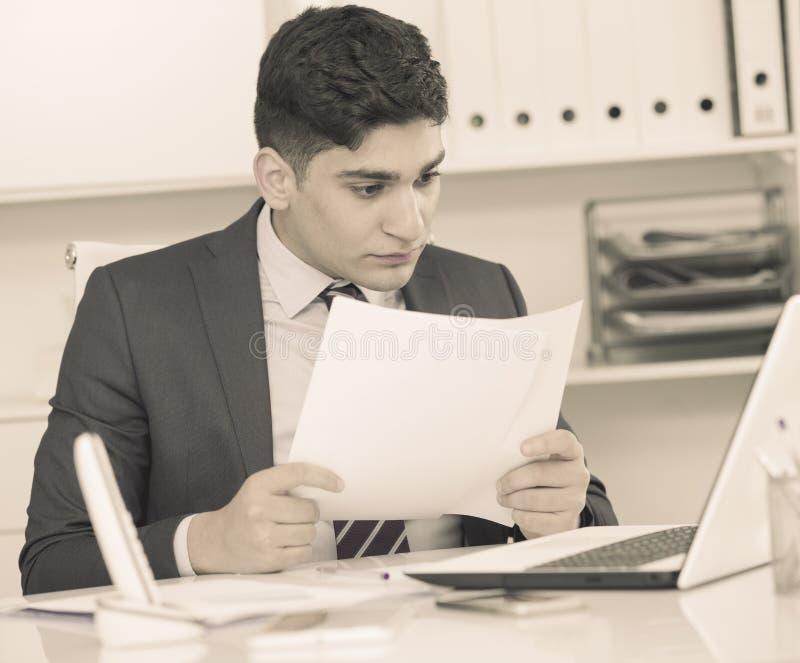 Ο διευθυντής διαβάζει τα έγγραφα για τη συναλλαγή στοκ φωτογραφία με δικαίωμα ελεύθερης χρήσης