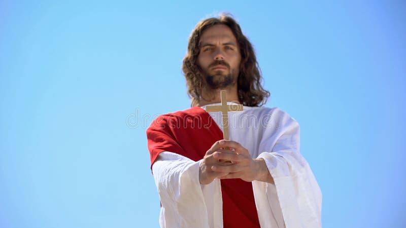 Ο Ιησούς κρατά ξύλινο σταυρό ενάντια στον γαλάζιο ουρανό, μετατροπή σε Χριστιανισμό, βάπτισμα στοκ εικόνα με δικαίωμα ελεύθερης χρήσης