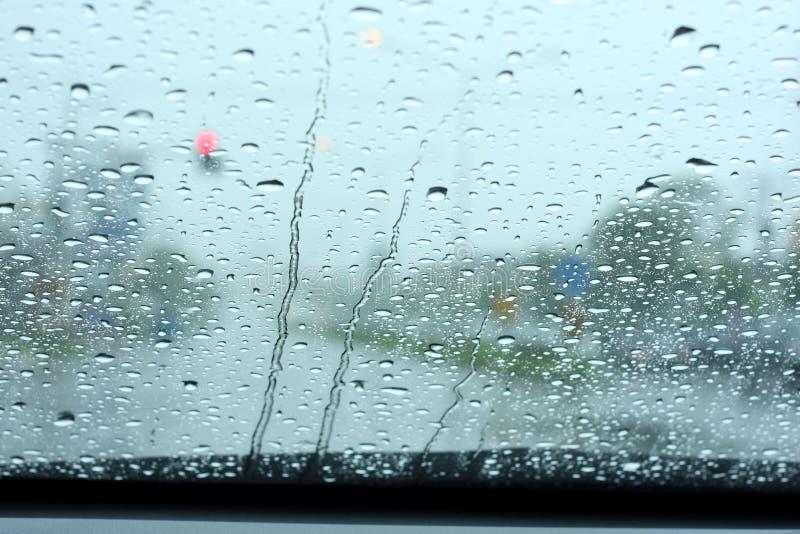 Οδική άποψη μέσω του παραθύρου αυτοκινήτων με τις πτώσεις βροχής στοκ εικόνες