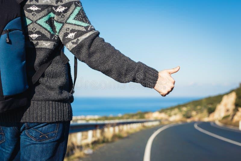 Οδικό ταξίδι, ταξίδι, χειρονομία και έννοια ανθρώπων - hitchhiker που σταματά το αυτοκίνητο με τους αντίχειρες επάνω στο σημάδι χ στοκ εικόνα