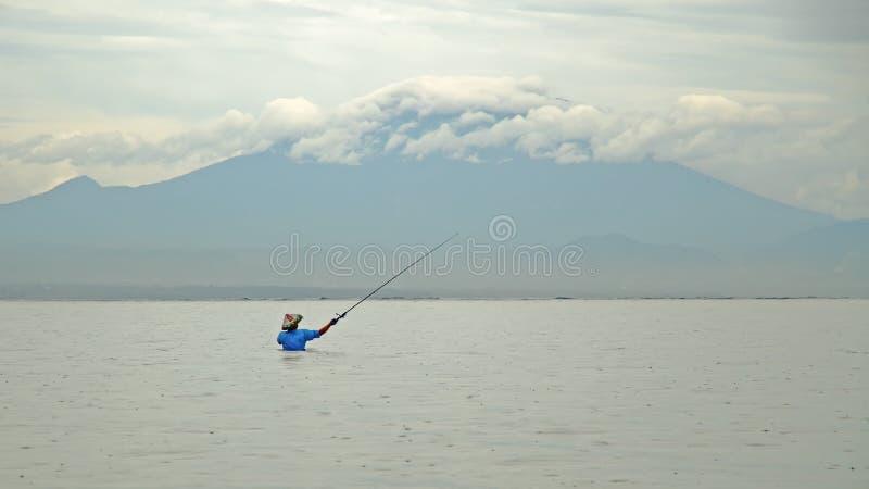 Ο ινδονησιακός ψαράς πιάνει ένα ψάρι κατά τη διάρκεια στοκ φωτογραφίες