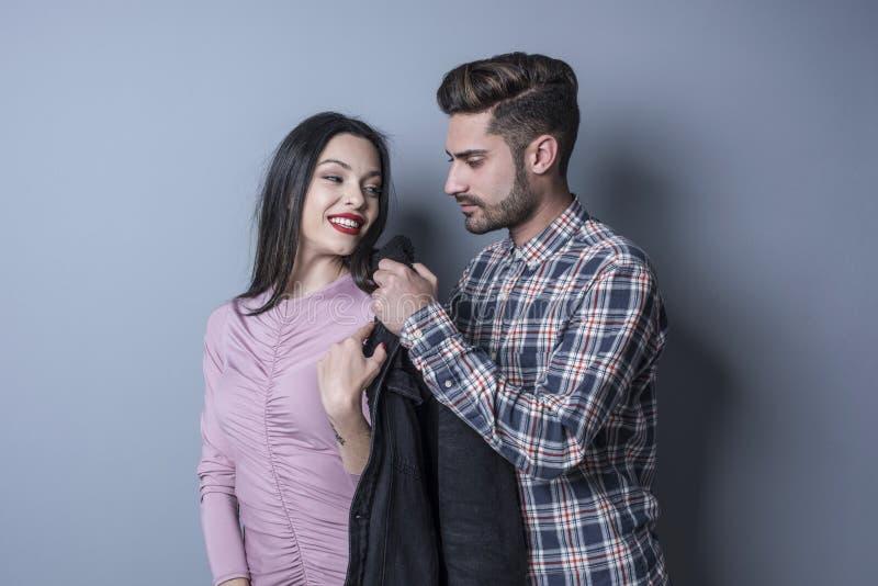 Ο ιπποτικός άνδρας προσφέρει ένα πουκάμισο σε μια γυναίκα brunette στοκ εικόνες