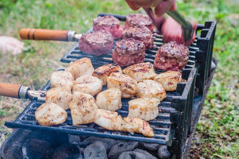 Ολισθαίνοντες ρυθμιστές βόειου κρέατος Sizzling και όστρακα θάλασσας που ψήνουν στη σχάρα σε ένα hibachi ξυλάνθρακα στοκ φωτογραφία με δικαίωμα ελεύθερης χρήσης