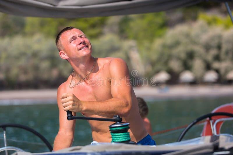 Ο ιστιοπλόος γυρίζει το πανί ελέγχου σχοινιών βαρούλκων στην πλέοντας βάρκα αθλητισμός στοκ εικόνες με δικαίωμα ελεύθερης χρήσης