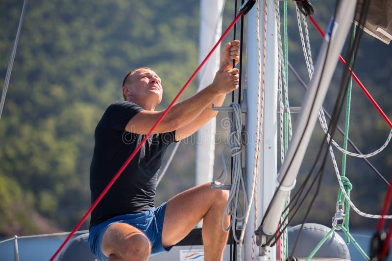 Ο ιστιοπλόος τραβά το σχοινί ελέγχοντας το πανί στην πλέοντας βάρκα αθλητισμός στοκ εικόνες