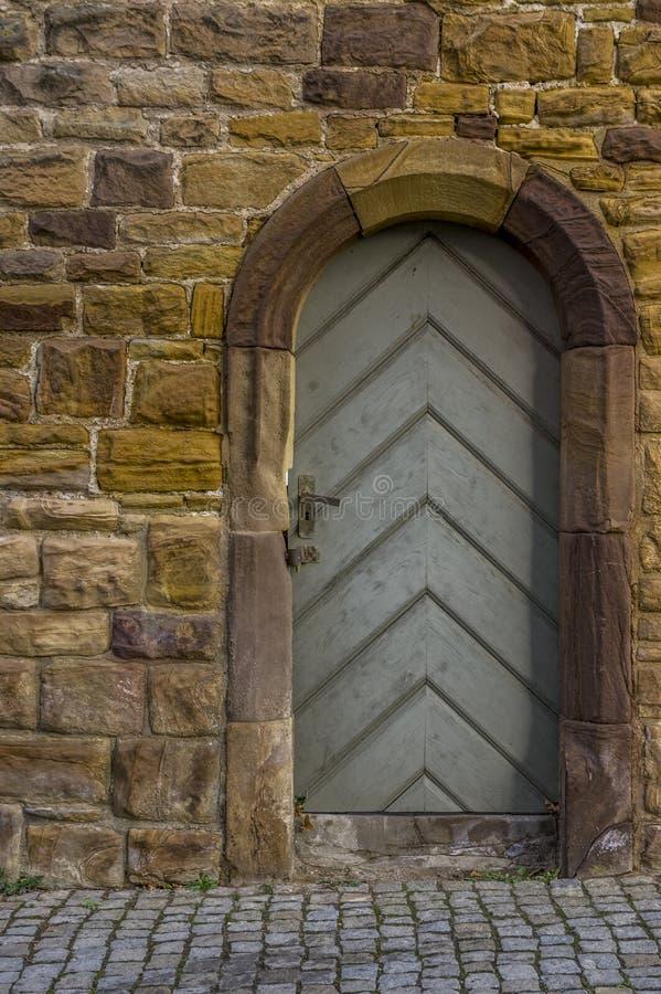 Ο ιστορικός τοίχος πόλεων ψαμμίτη με την ξύλινη πόρτα και το πλαίσιο πορτών με τον ψαμμίτη γύρω από την αψίδα χάρασαν με την ειδι στοκ φωτογραφίες με δικαίωμα ελεύθερης χρήσης