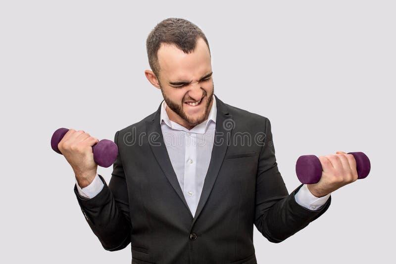 Ο ισχυρός και καλοχτισμένος νεαρός άνδρας στη στάση κοστουμιών και κρατά δύο dumbells στα χέρια Ασκεί σκληρά Απομονωμένος στο λευ στοκ εικόνες