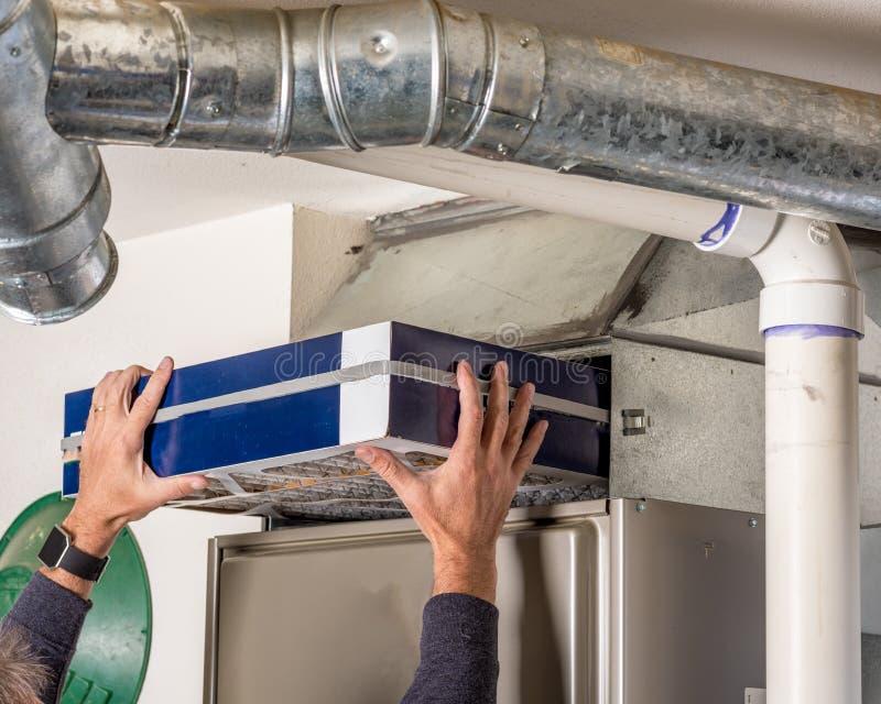 Ο ιδιοκτήτης σπιτιού αντικαθιστά το φίλτρο στο φούρνο τους στοκ φωτογραφίες