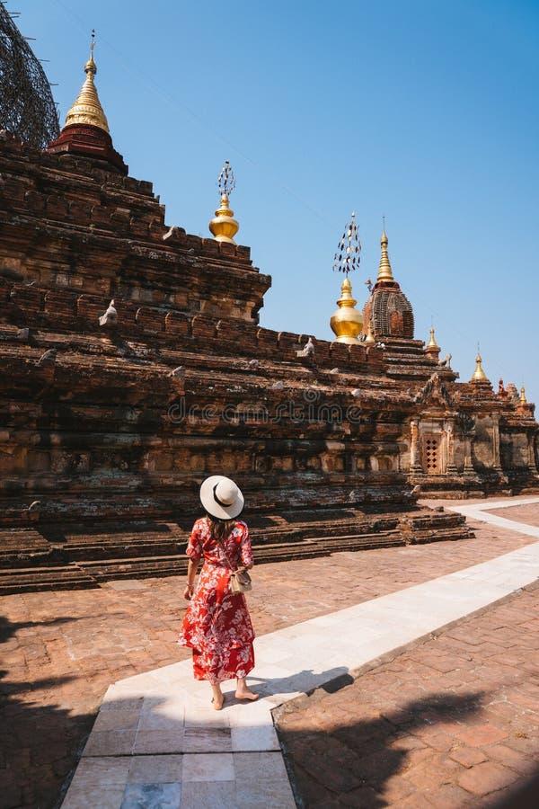 Ο κάθετος πυροβολισμός ενός θηλυκού με ένα κόκκινο φόρεμα που περπατά κοντά σε έναν ναό μια ηλιόλουστη ημέρα στο Μιανμάρ, άρχισε στοκ εικόνα με δικαίωμα ελεύθερης χρήσης
