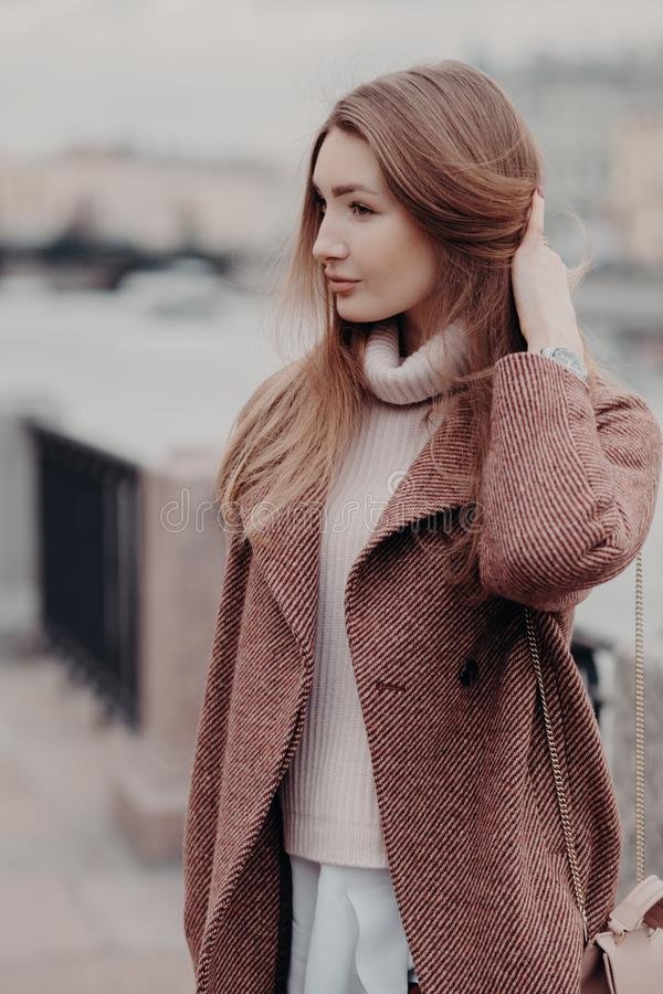 Ο κάθετος πυροβολισμός της μοντέρνης γυναίκας Caucasain κοιτάζει κατά μέρος, φορά το μοντέρνο θερμό παλτό, θέτει υπαίθριο, απολαμ στοκ εικόνα με δικαίωμα ελεύθερης χρήσης