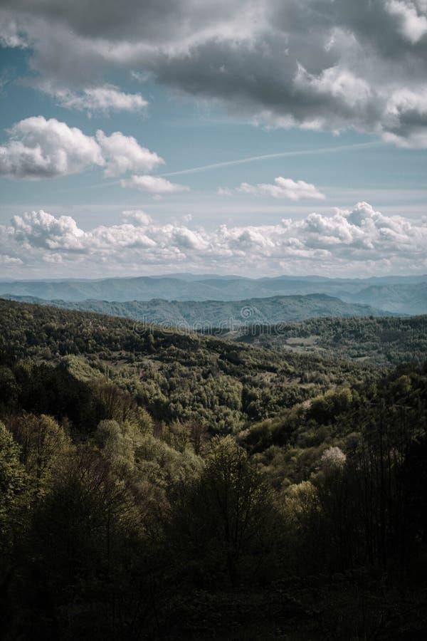 Ο κάθετος πυροβολισμός των όμορφων βουνών και των λόφων με την κατάπληξη καλύπτει στον ουρανό στοκ φωτογραφίες