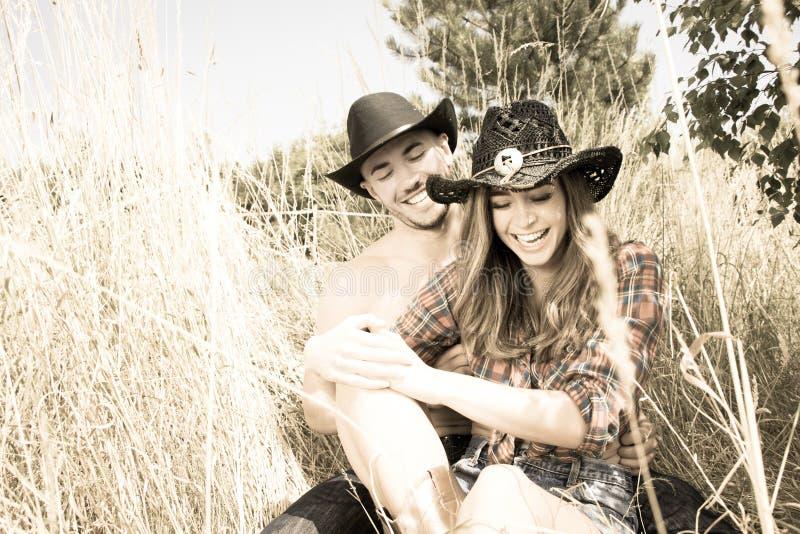 Ο κάουμποϋ και cowgirl συνδέει τη συνεδρίαση στη χλόη, γελώντας δεδομένου ότι αυτοί γαργάλημα μεταξύ τους στοκ εικόνες