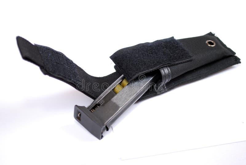 Ο κάτοχος καταστημάτων φόρτωσε με τις κασέτες από ένα πυροβόλο όπλο σε μια μαύρη σακούλα κασετών υφάσματος σε ένα άσπρο υπόβαθρο στοκ φωτογραφία με δικαίωμα ελεύθερης χρήσης