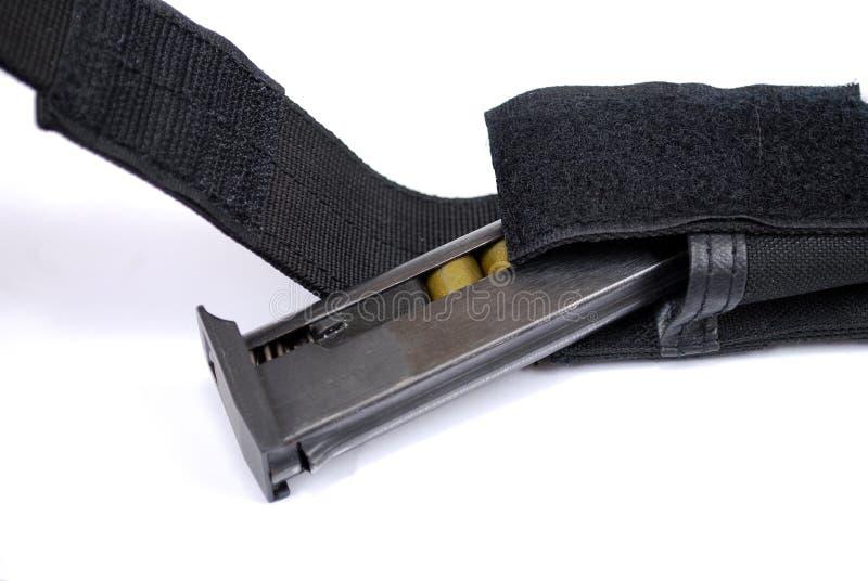 Ο κάτοχος καταστημάτων φόρτωσε με τις κασέτες από ένα πυροβόλο όπλο σε μια μαύρη σακούλα κασετών υφάσματος σε ένα άσπρο υπόβαθρο στοκ φωτογραφίες με δικαίωμα ελεύθερης χρήσης