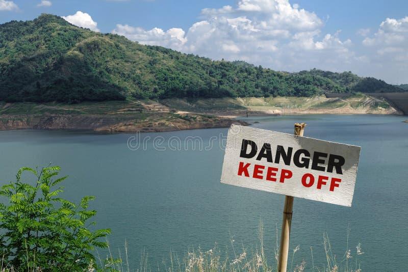 Ο κίνδυνος αποφεύγει το σημάδι με τη λίμνη φραγμάτων στοκ εικόνες