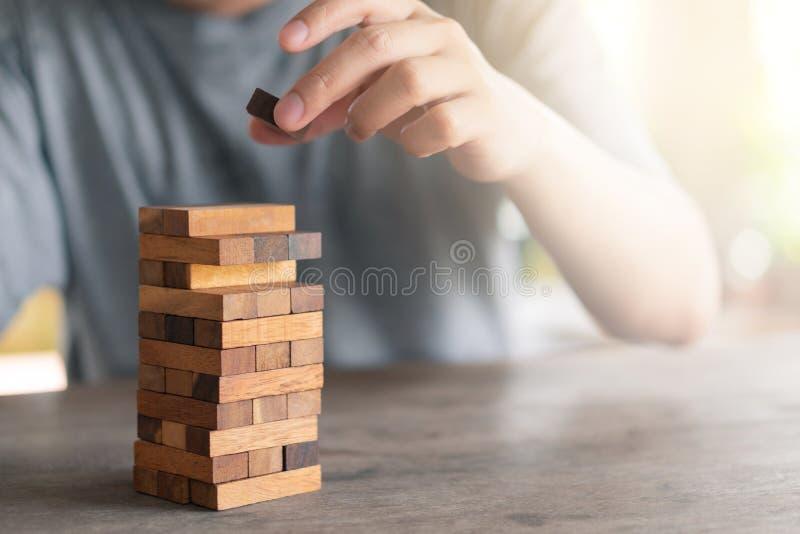 Ο κίνδυνος θα συμβεί Χέρι του μηχανικού που παίζει ένα ξύλινο παιχνίδι φραγμών στοκ εικόνες