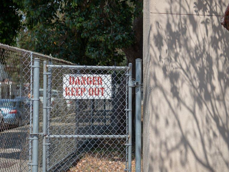 Ο κίνδυνος κρατά έξω το σημάδι πίσω από έναν κατοικημένο φράκτη συνδέσεων αλυσίδων στη κατοικήσιμη περιοχή στοκ εικόνα