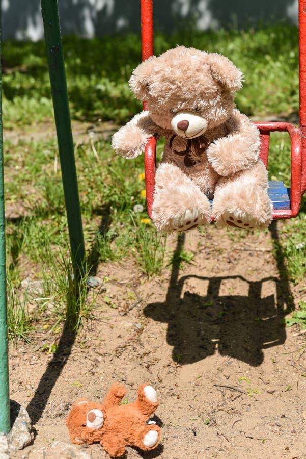 Ο κίνδυνος του μειωμένου παιδιού, teddy αρκούδα μειώθηκε στο έδαφος από μια παλαιά ταλάντευση στοκ φωτογραφίες