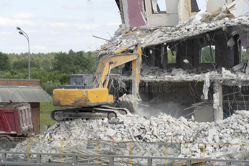 Ο κίτρινος εκσκαφέας παίρνει τα απόβλητα κατασκευής για τη φόρτωση επάνω σε ένα φορτηγό Η τεχνική κατέστρεψε το κτήριο, είναι ενί στοκ φωτογραφία