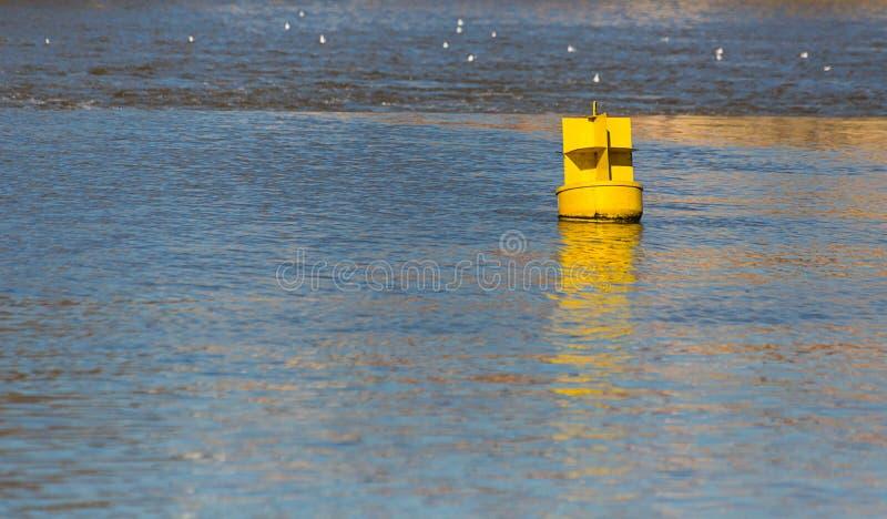 Ο κίτρινος σημαντήρας σιδήρου επιπλέει στο μπλε νερό που ο ποταμός παρουσιάζει το επίπεδο των σκαφών στοκ φωτογραφία με δικαίωμα ελεύθερης χρήσης