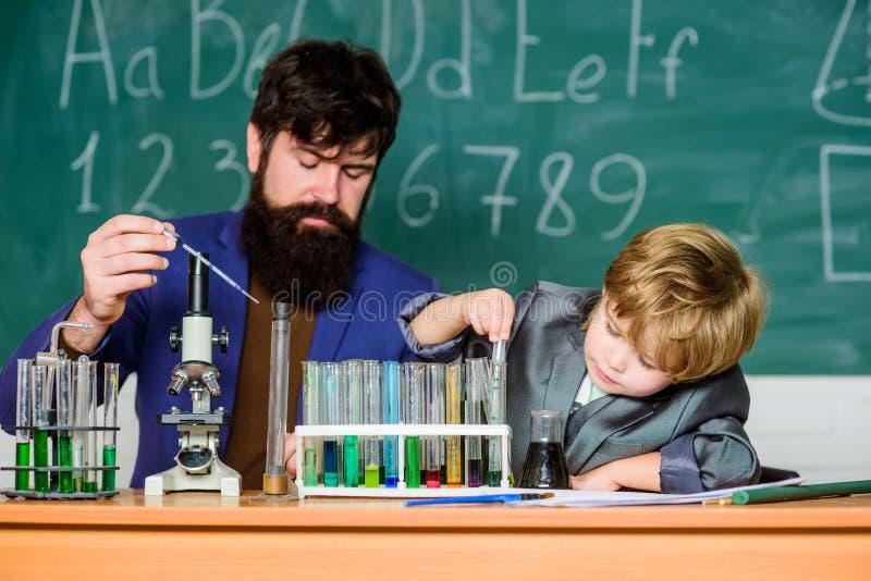 Ο καθένας επιτυχής καθημερινός Η βιολογία χημείας και φυσικής Φρόνηση o μικρό αγόρι με το άτομο δασκάλων Φιάλη στοκ φωτογραφίες με δικαίωμα ελεύθερης χρήσης