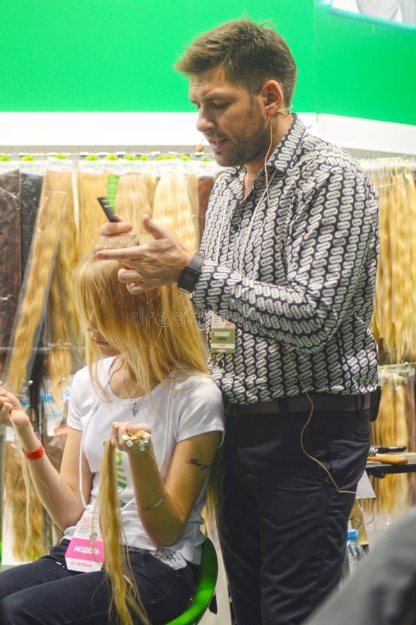 Ο καθιερώνων τη μόδα κύριος κουρέας κάνει ένα μοντέρνο updo τη νέα ξανθή τρίχα γυναικών να παρουσιάσει στοκ εικόνες με δικαίωμα ελεύθερης χρήσης
