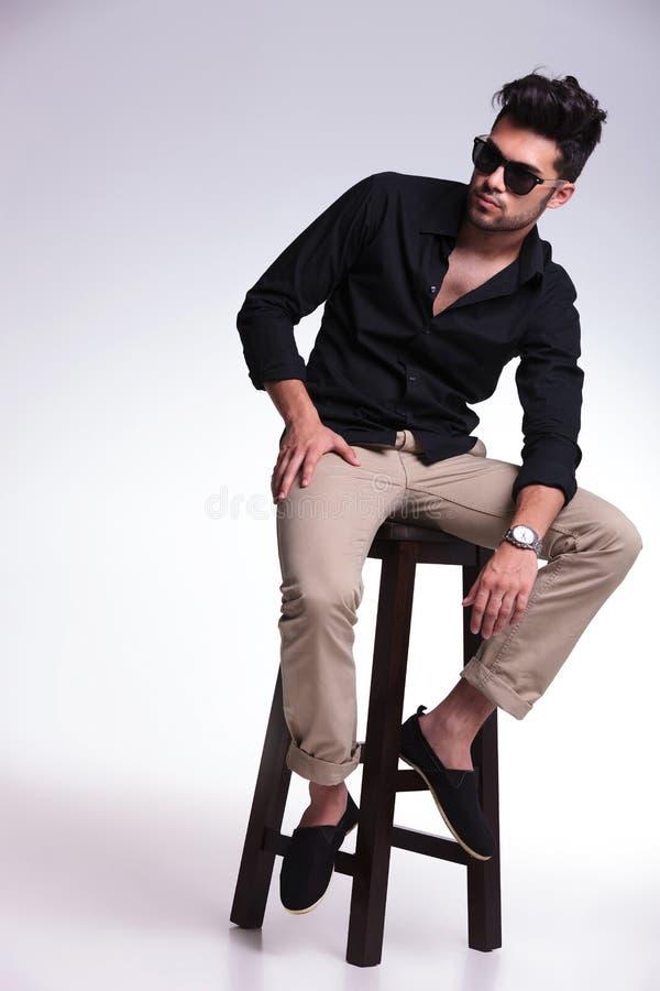 Ο καθισμένος νεαρός άνδρας κοιτάζει μακρυά από τη κάμερα στοκ εικόνα