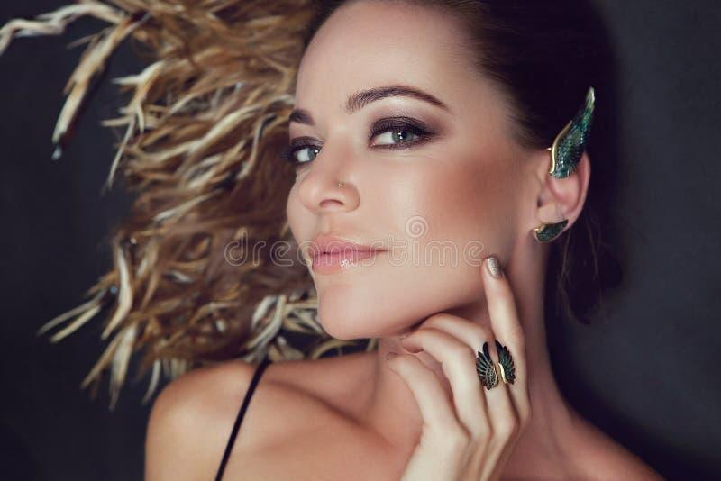 Ο καλλιεργημένος πυροβολισμός πλάγιας όψης της γυναίκας με τέλειο αποτελεί φορά το ασημένιο σκουλαρίκι μανσετών στη μορφή ενός φτ στοκ φωτογραφίες