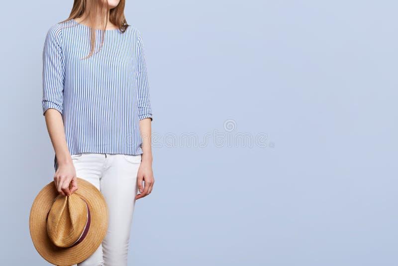 Ο καλλιεργημένος πυροβολισμός του unrecognizable θηλυκού wers που η ριγωτή μπλούζα και το άσπρο παντελόνι, κρατούν το καπέλο αχύρ στοκ φωτογραφίες