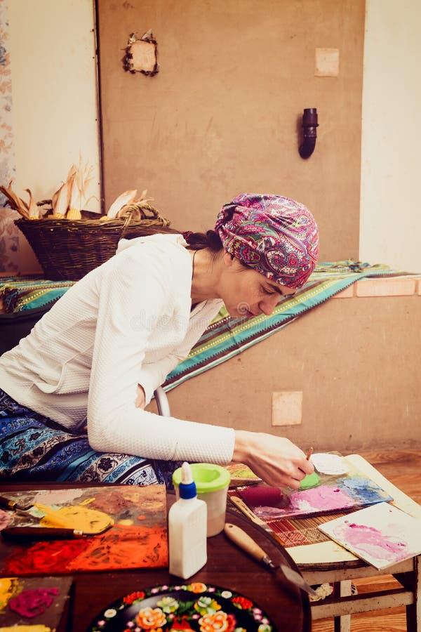 Ο καλλιτέχνης είναι δημιουργεί τη διάσημη ζωγραφική Petrikovsky στοκ εικόνες με δικαίωμα ελεύθερης χρήσης