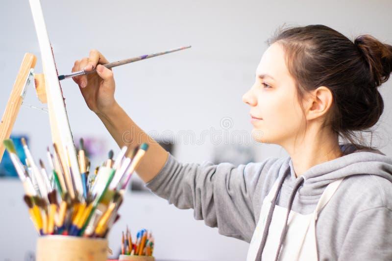 Ο καλλιτέχνης κοριτσιών χρωματίζει μια εικόνα στον καμβά στοκ εικόνα