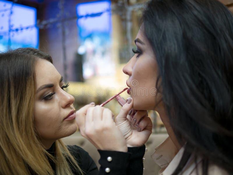 Ο καλλιτέχνης σύνθεσης makeup στην όμορφη νέα γυναίκα στο εσωτερικό επαγγελματικά χείλια χρωμάτων με το κραγιόν στοκ εικόνα