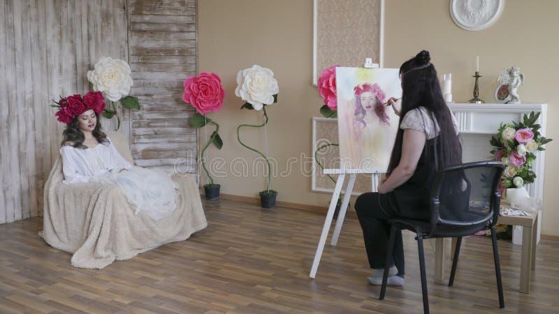 Ο καλλιτέχνης σύρει ένα πορτρέτο από τη φύση Όμορφο πρότυπο, με ένα στεφάνι των ερυθρών peonies σε επικεφαλής του, που θέτει τη σ στοκ φωτογραφία με δικαίωμα ελεύθερης χρήσης