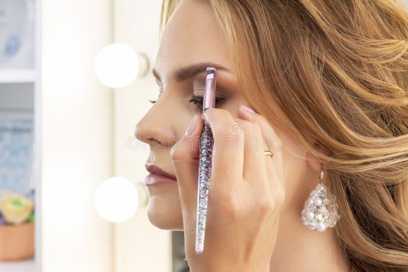 Ο καλλιτέχνης Makeup βάζει makeup στο πρότυπο κοριτσιών Η βούρτσα εφαρμόζει τη σκιά ματιών στα φρύδια όμορφο πρότυπο κοριτσιών, π στοκ φωτογραφία με δικαίωμα ελεύθερης χρήσης