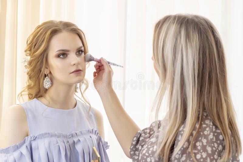 Ο καλλιτέχνης Makeup βάζει makeup στο πρότυπο κοριτσιών Η βούρτσα εφαρμόζει τις σκιές, concealer όμορφο πρότυπο κοριτσιών, πορτρέ στοκ εικόνες