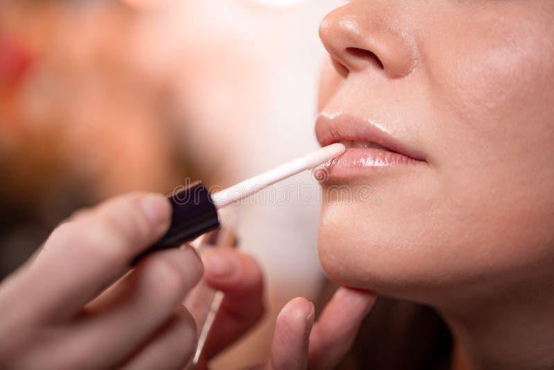 Ο καλλιτέχνης Makeup εφαρμόζει το κόκκινο κραγιόν Όμορφο πρόσωπο γυναικών Χέρι του κυρίου σύνθεσης, χείλια ζωγραφικής του νέου πρ στοκ εικόνες με δικαίωμα ελεύθερης χρήσης