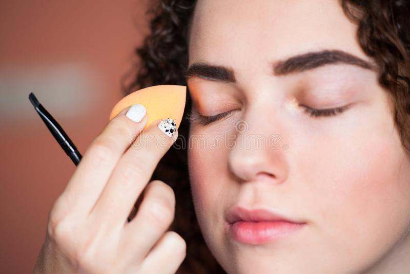 Ο καλλιτέχνης Makeup εφαρμόζει το skintone Όμορφο πρόσωπο γυναικών καλλιτεχνών σφουγγαριών makeup Ίδρυμα Skincare στοκ εικόνα