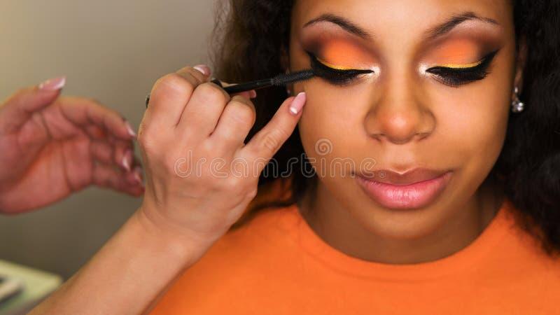 Ο καλλιτέχνης Makeup ισχύει makeup στο πρόσωπο του κοριτσιού στοκ εικόνα