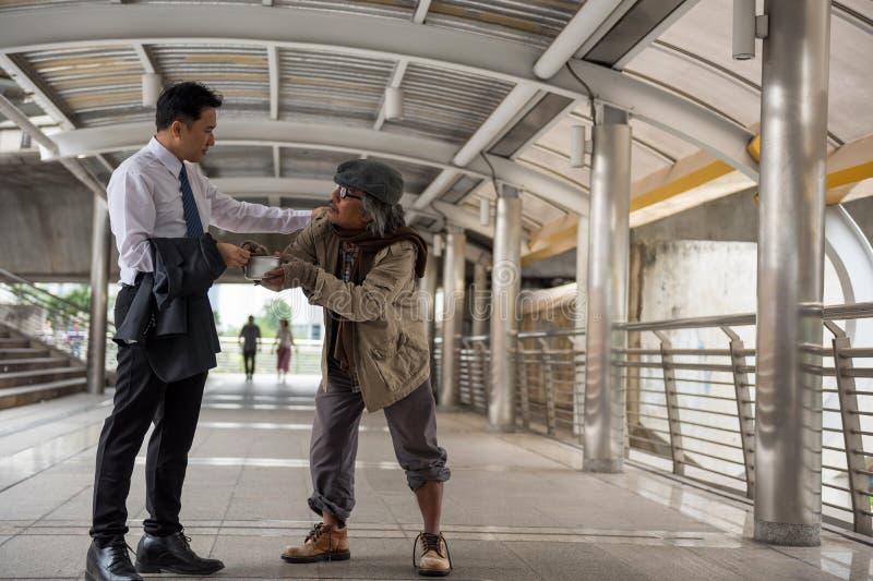 Ο καλός επιχειρηματίας δίνει τα χρήματα στους αστέγους στοκ φωτογραφία με δικαίωμα ελεύθερης χρήσης