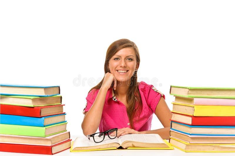 Ο καλός σπουδαστής κάθεται στο γραφείο της με μια στοίβα των βιβλίων, ISO στοκ φωτογραφίες
