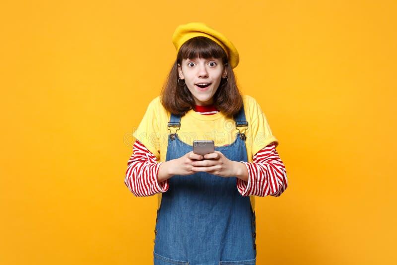 Ο κατάπληκτος έφηβος κοριτσιών γαλλικό beret, τζιν sundress που χρησιμοποιεί το κινητό τηλέφωνο, δακτυλογραφώντας sms το μήνυμα α στοκ εικόνες με δικαίωμα ελεύθερης χρήσης